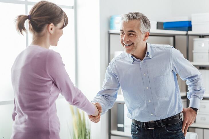 Håndtrykk mellom eldre mann og yngre kvinne