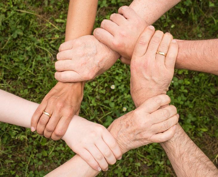 Kollegahjelpsordningen - armer over gress som holder hverandre i trygt grep