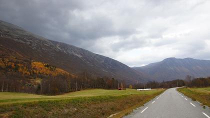 Vei i dal med fjell i bakgrunnen. Høstlandskap